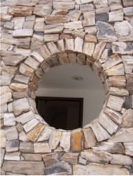 錆バラの外壁に丸い開口がアクセントに